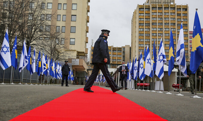 """A Kosovo police officer walks across a red carpet prior to a ceremony held digitally, in the capital Pristina, Monday, Feb. 1, 2021. Kosovo and Israel formally have established diplomatic ties in a ceremony held digitally due to the pandemic lockdown. Kosovo's Foreign Minister Meliza Haradinaj-Stublla and her Israeli counterpart Gabriel Ashkenazi on Monday held a virtual ceremony signing the documents. The two countries considered it as """"making history"""" and marking """"a new chapter."""" (AP Photo/Visar Kryeziu)"""