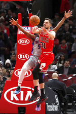 Chicago Bulls' Tomas Satoransky, right, passes under pressure from Detroit Pistons' Langston Galloway, left, during the first half of an NBA basketball game Wednesday, Nov. 20, 2019, in Chicago. (AP Photo/Charles Rex Arbogast)