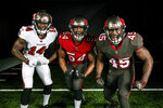 In this handout released by the Tampa Bay Buccaneers Tuesday, April 7, 2020, from left, wide receiver Chris Godwin, linebacker Lavonte David, and linebacker Devin White, wear the team's new uniforms that they will debut during the 2020 NFL football season. (Tampa Bay Buccaneers via AP)