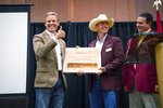 This photo provided by the State of Tennessee shows Tennessee Gov. Bill Lee receiving an award from Dustin Pearson, Tennessee Cattlemen's Association President-Elect at the Tennessee Cattlemen's Association annual convention on July 30, 2021 in Sevierville, Tenn. Despite having some of the lowest COVID-19 vaccination rates in the country, Tennessee isn't planning to offer any incentives for people to get the shot. But it's a different story when it comes to cattle, where the state has reimbursed farmers nearly half a million dollars over the past two years to vaccinate their herds against respiratory and other diseases. At right is Jay Yeargin, Tennessee Cattlemen's Association President. (State of Tennessee via AP)