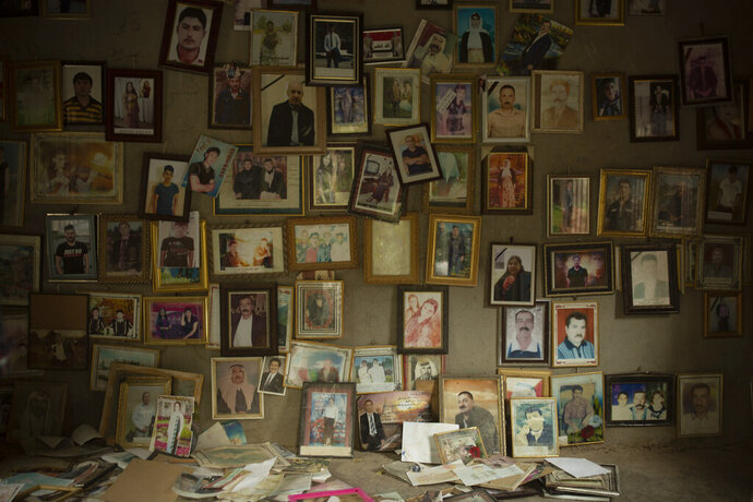 In this Sept. 12, 2019 photo, pictures of Yazidis slain in 2014 by Islamic State militants are found in a small room at the Lalish shrine in northern Iraq. When Yazidis were seized alive by the militants, top commanders registered them, photographed the women and children, categorized them into married, unmarried and girls, and decided where they would be sent. Initially, the thousands of captured women and children were handed out as gifts to fighters who took part in the Sinjar offensive, in line with the group's policy on the