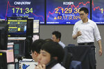 A currency trader passes by screens showing the Korea Composite Stock Price Index, right, and the foreign exchange rate at the foreign exchange dealing room of the KEB Hana Bank headquarters in Seoul, South Korea, Wednesday, June 3, 2020. Asian shares are rising after Wall Street extended its gains for the third straight day, driven by optimism over economies reopening from shutdowns to stem the coronavirus pandemic. (AP Photo/Ahn Young-joon)