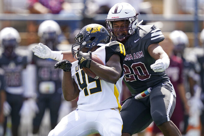 Arkansas-Pine Bluff running back Mattias Clark (45) is tackled for a loss by Alabama A&M linebacker Armoni Holloway (20) during the first half of the Southwestern Athletic Conference NCAA college football game, Saturday, May 1, 2021, in Jackson, Miss. (AP Photo/Rogelio V. Solis)