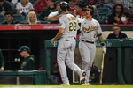 Oakland Athletics' Matt Olson (28) celebrates with Yan Gomes after scoring off of a ground out by Seth Brown during the sixth inning of a baseball game against the Los Angeles Angels Friday, Sept. 17, 2021, in Anaheim, Calif. (AP Photo/Ashley Landis)