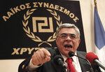In this May 6, 2012 file photo, extreme right Golden Dawn party leader Nikos Mihaloliakos speaks during a news conference in front of a banner with the twisting Maeander, an ancient Greek decorative motif that the party has adopted as its symbol, in Athens. Golden Dawn, the far-right, anti-immigrant party that had shocked Greek politics by evolving from a marginal, violent neo-Nazi group into Greece's third-largest party during the country's economic crisis, was knocked out of Parliament in Sunday's national election. (AP Photo/Petros Giannakouris, file)