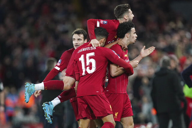 Liverpool's Curtis Jones, right, celebrates with his teammates after scoring his side's opening goal during the English FA Cup third round soccer match between Liverpool and Everton at Anfield stadium in Liverpool, England, Sunday, Jan. 5, 2020. (AP Photo/Jon Super)