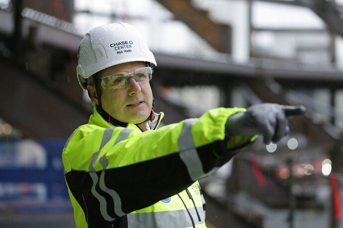 In this photo taken Jan. 24, 2018, Golden State Warriors President and COO Rick Welts looks out at Chase Center under construction in San Francisco. Standing in the rain seven stories above the concrete, construction workers, steel and mud, Rick Welts is beaming at an arena project that is absolutely his baby. The Warriors COO has been entrusted by owners Joe Lacob and Peter Guber to be the unofficial foreman as Chase Center goes up in the Mission Bay district of San Francisco for a scheduled opening of late summer 2019. And with a goal of becoming one of the top notch entertainment venues in the world, right up with The O2 in London and Madison Square Garden for attracting the best music shows. (AP Photo/Eric Risberg)