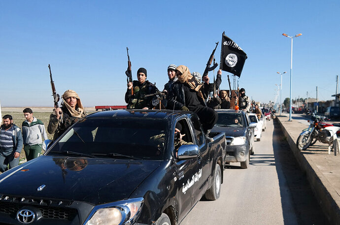 FILE - In this this file photo released on May 4, 2015, on a militant website, which has been verified and is consistent with other AP reporting, Islamic State militants pass by a convoy in Tel Abyad, northeast Syria.   The Washington-based Syria Justice and Accountability Center, a U.S.-based Syrian rights group, said Thursday, Jan. 16, 2020,  that evidence, documents produced by the Islamic State militants themselves,  could help identify individuals responsible for atrocities during the militants four-year reign of terror in Syria, thus enabling prosecution for international crimes. (Militant website via AP, File)