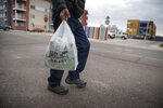 FILE - In this Jan. 10, 2019, file photo a shopper carries groceries in a plastic bag after shopping at the Silver Street Market in downtown Albuquerque, N.M. Businesses in New Mexico's largest metropolitan area are preparing for rules that will take effect with the start of the new year that call for banning plastic bags. (Roberto E. Rosales/The Albuquerque Journal via AP, File)