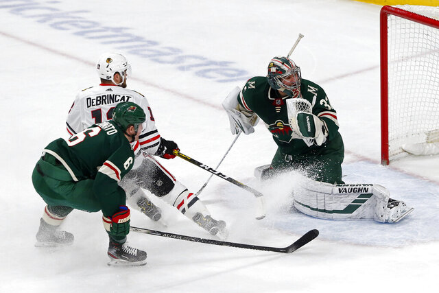Minnesota Wild's Alex Stalock, right, watches as a shot by Chicago Blackhawks' Alex DeBrincat, left, goes wide in the first period of an NHL hockey game Tuesday, Feb. 4, 2020, in St. Paul, Minn. (AP Photo/Jim Mone)