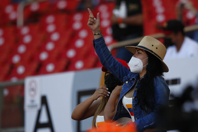 A fan of Venezuela wearing a face mask, cheers for her team during a Caribbean Series baseball game against Panama at Teodoro Mariscal Stadium in Mazatlan, Mexico, Sunday, Jan. 31, 2021. (AP Photo/Moises Castillo)