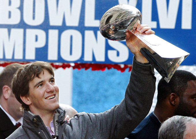 File-This Feb. 7, 2012, file photo shows New York Giants quarterback Eli Manning holding up the Vince Lombardi Trophy during the team's NFL football Super Bowl parade in New York. The man who has been the face of the New York Giants since 2004 is probably going to make his final appearance this weekend. Manning's 16-year Giants' career that has included two Super Bowl titles likely will come to an end Sunday, Dec. 29, 2019, when New York tries to spoil the Philadelphia Eagles bid to win the NFC East. (AP Photo/Julio Cortez,File)