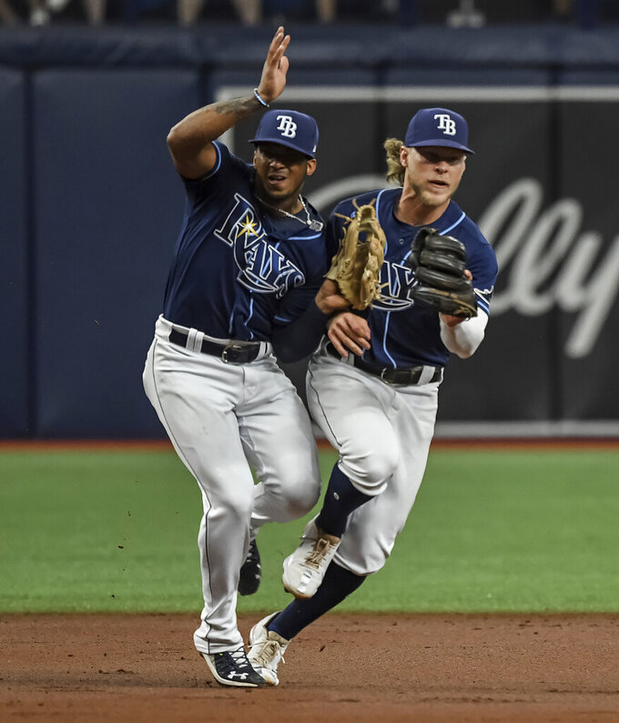 Tampa Bay Rays third baseman Wander Franco, left, collides with shortstop Taylor Walls on a ground ball hit by Cleveland Indians' Oscar Mercado during the third inning in the second baseball game of a doubleheader Wednesday, July 7, 2021, in St. Petersburg, Fla.(AP Photo/Steve Nesius)