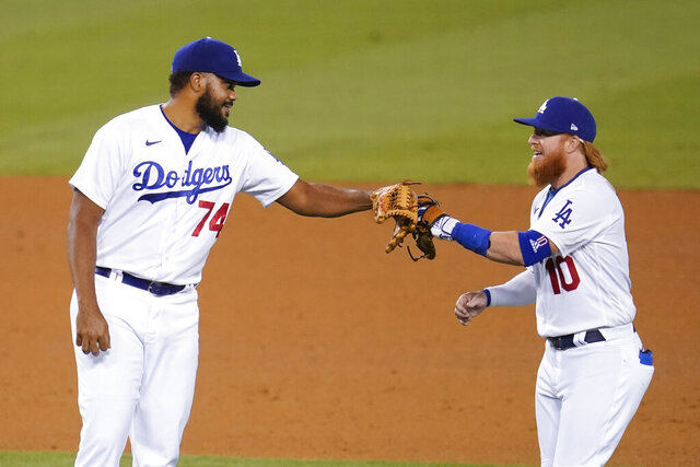 Los Angeles Dodgers' Kenley Jansen (74) and Justin Turner celebrate after the team's 6-0 win over the San Diego Padres in a baseball game Wednesday, Aug. 12, 2020, in Los Angeles. (AP Photo/Marcio Jose Sanchez)