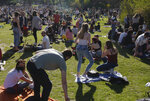 People sit on the grass in the Vauban park in Lille, northern France, Tuesday, March 30, 2021. The number of patients in intensive care in France on Monday surpassed the worst point of the country's last coronavirus surge in the autumn of 2020, another indicator of how a renewed crush of infections is bearing down on French hospitals. (AP Photo/Michel Spingler)