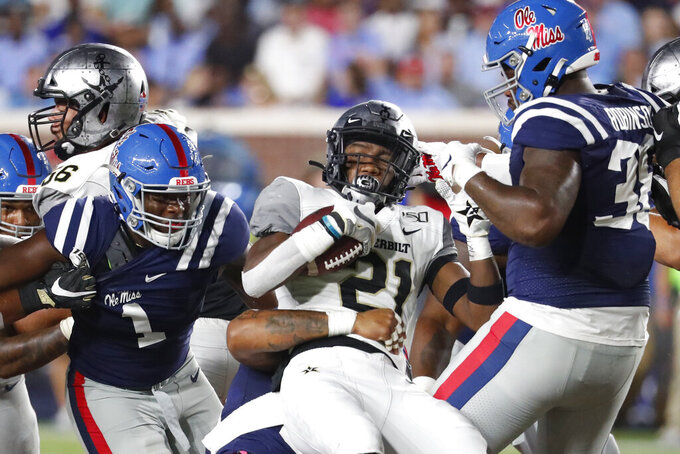 Mississippi linebacker Lakia Henry (1) and defensive end Austrian Robinson (38) help tackle Vanderbilt running back Keyon Brooks (21) during the first half of an NCAA college football game in Oxford, Miss., Saturday, Oct. 5, 2019. (AP Photo/Rogelio V. Solis)