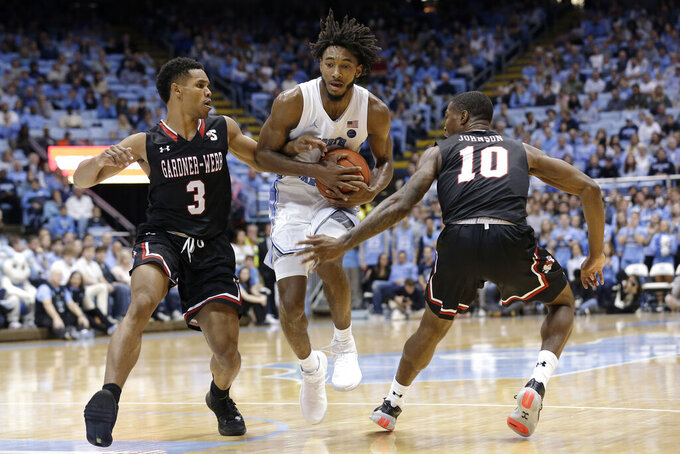 North Carolina guard Leaky Black (1) drives between Gardner-Webb guards Justin Jenkins (3) and Nate Johnson (10) during the first half of an NCAA college basketball game in Chapel Hill, N.C., Friday, Nov. 15, 2019. (AP Photo/Gerry Broome)