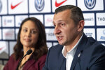 FILE - In this Oct. 28, 2019, file photo, General Manager of the United States women's national soccer team Kate Markgraf, left, listens as head coach Vlatko Andonovski speaks during a news conference in New York. Twenty players have been named to the U.S. women's soccer team that will play for a spot in the Tokyo Olympics. Coach Andonovski announced the roster for the CONCACAF Olympic qualifying tournament Friday, Jan. 17, 2020. (AP Photo/Mary Altaffer)