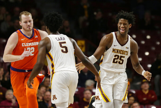 Minnesota center Daniel Orturu (25) celebrates as score with guard Marcus Carr (5) while Clemson forward Paul Grinde (32) runs downcourt in the second half during an NCAA college basketball game Monday, Dec. 2, 2019, in Minneapolis. (AP Photo/Andy Clayton-King)