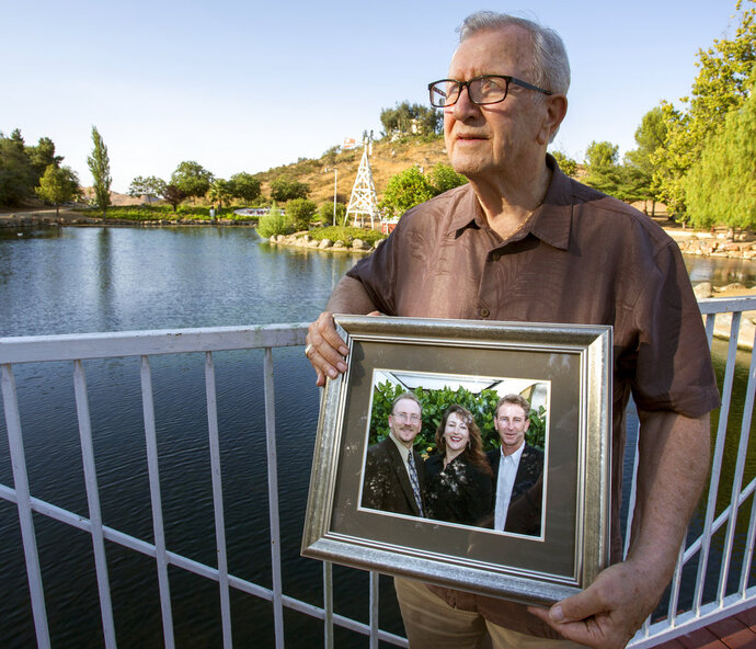 FILE - In this Friday, June 23, 2017, file photo, Frank Kerrigan holds onto a photograph of his three children John, Carole, and Frank, near Wildomar, Calif. A family who thought they had buried their loved one only to found out he was alive 11 days after his funeral is now suing the California county responsible for what they say started as a mix-up but became a cover-up.  (Andrew Foulk/The Orange County Register via AP, File)
