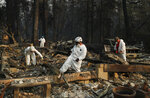 FILE- In this Friday, Nov. 16, 2018, file photo search and rescue personnel search a home for human remains in the aftermath of the Camp fire in Paradise, Calif. Northern California crews battling the country's deadliest wildfire in a century were bracing for strong winds Sunday, Nov. 18, that could erode gains they have made in containing the fearsome blaze, which has killed dozens and leveled a town. (AP Photo/John Locher, File)