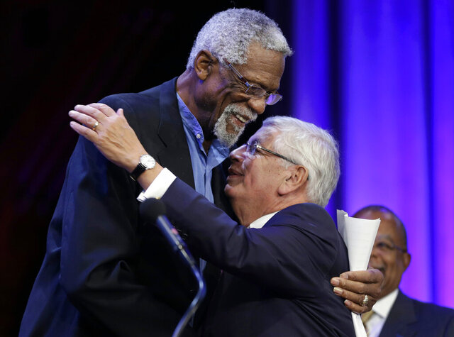 FILE - In this Wednesday, Oct. 2, 2013 file photo, Former Boston Celtics basketball player Bill Russell, left, hugs National Basketball Association Commissioner David Stern during an award ceremony for the W.E.B. Du Bois Medal at Harvard University, in Cambridge, Mass. David Stern, who spent 30 years as the NBA's longest-serving commissioner and oversaw its growth into a global power, has died on New Year's Day, Wednesday, Jan. 1, 2020. He was 77.  (AP Photo/Steven Senne, FGile)