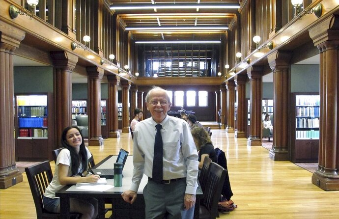 In this Aug. 28, 2019 photo, University of Vermont Professor Wolfgang Mieder poses in the school's library in Burlington, Vt., where his vast collection of books on proverbs are now housed in a new collection. The preeminent proverb scholar had been concerned about what would happen to his extensive collection on proverbs if something happened to him. (AP Photo/Lisa Rathke)