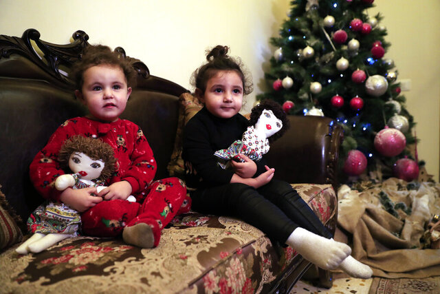 Sama Chlawuit, left, and her sister Sima-Rita, whose family home had the windows blown out during August's massive explosion in Beirut, hold their dolls at their grandfather's home, in Beirut, Lebanon, Tuesday, Dec. 29, 2020. After the explosion, painter Yolande Labaki made 100 dolls for children affected by the destruction. (AP Photo/Hussein Malla)