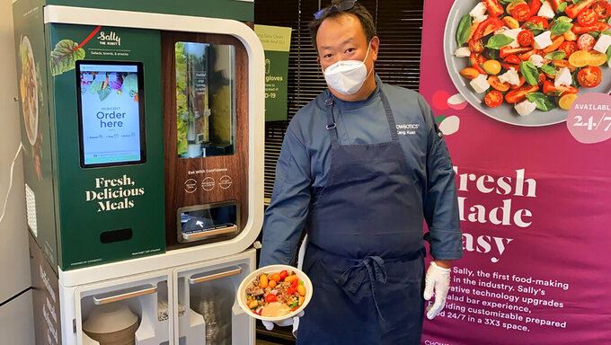 Kang Kuan, vice president of culinary at Chowbotics, holds a custom salad made by his company's robotic salad-making kiosk at the company's headquarters in Hayward, Calif., on Tuesday, June 23, 2020. Prior to this year, Chowbotics had sold over 100 of its $35,000 robots, primarily to hospitals and colleges. But since the coronavirus hit, sales have jumped more than 60%, CEO Rick Wilmer said, with growing interest from grocery stores, senior living communities and even the U.S. Department of Defense. (AP Photo/Terry Chea)