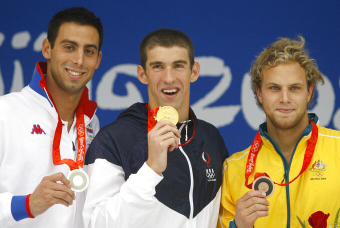 """File-Gold medalist United States' Michael Phelps, center, reacts during the presentation ceremony for the men's 100-meter butterfly final during the swimming competitions in the National Aquatics Center at the Beijing 2008 Olympics in Beijing, Saturday, Aug. 16, 2008. At left is Serbia's Milorad Cavic, who took silver and and at right is bronze medalist Andrew Lauterstein from Australia. The Olympics are remembered for the stars. That was true in Beijing in 2008, and the stars were Phelps and Usain Bolt. But Beijing is also storied for its signature venues like the """"Bird's Nest"""" stadium, and the """"Water Cube"""" swimming venue. No Olympics before — or since — have impacted a city the way the Olympics did Beijing. (AP Photo/Mark Baker, File)"""