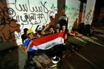 """In this Oct. 31, 2019, photo, Iraqi anti-government protesters spend the night in a building near Tahrir Square, Baghdad, Iraq. An abandoned building in central Baghdad has emerged as the epicenter of anti-government protests in Iraq, with hundreds holed up inside. The Saddam Hussein-era building known as the """"Turkish Restaurant"""" overlooks Tahrir Square, the Tigris River and the Green Zone, and protesters who took it over on Oct. 25 have sworn not to leave it. (AP Photo/Hadi Mizban)"""