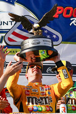 Kyle Busch raises the trophy after winning a NASCAR Cup Series auto race at Pocono Raceway, Sunday, June 27, 2021, in Long Pond, Pa. (AP Photo/Matt Slocum)
