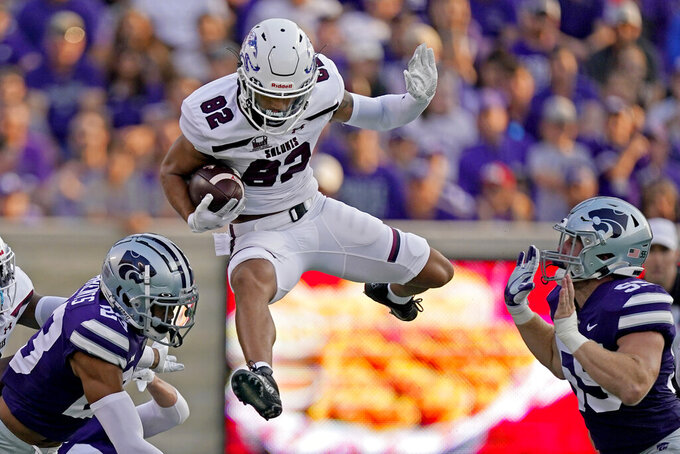 Southern Illinois wide receiver Izaiah Hartrup (82) jumps between Kansas State linebacker Cody Fletcher (55) and Kansas State defensive back Trey Krause (24) during the first half of an NCAA college football game, Saturday, Sept. 11, 2021, in Manhattan, Kan. (AP Photo/Charlie Riedel)