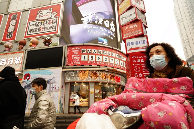 """Residents wearing masks past by a screen showing a trailer for the film """"Days and Nights in Wuhan"""" outside a mall in Wuhan in central China's Hubei province on Friday, Jan. 22, 2021. China is rolling out the state-backed film praising Wuhan ahead of the anniversary of the 76-day lockdown in the central Chinese city where the coronavirus was first detected. (AP Photo/Ng Han Guan)"""