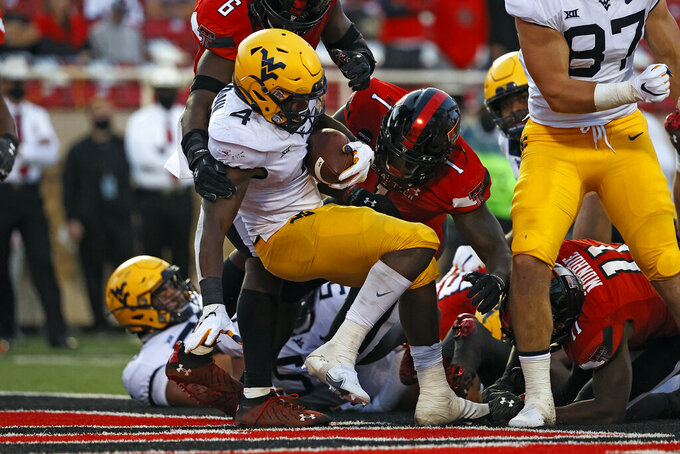West Virginia's Leddie Brown (4) scores a touchdown during the second half of an NCAA college football game against Texas Tech, Saturday, Oct. 24, 2020, in Lubbock, Texas. (AP Photo/Brad Tollefson)