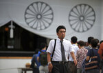 FILE - In this Aug. 13, 2015, file photo, Hidetoshi Tojo, the great-grandson of Hideki Tojo, wartime Japanese Prime Minister, walks after offering a payer at Yasukuni Shrine in Tokyo. Hidetoshi Tojo told The Associated Press that the absence of the remains has long been a humiliation for the bereaved families, but he's relieved the information has come to light.  (AP Photo/Eugene Hoshiko, File)