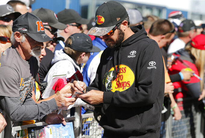 Driver Martin Truex Jr. signs autographs for fans prior to the start of the NASCAR Cup Series auto race at ISM Raceway, Sunday, March 10, 2019, in Avondale, Ariz. (AP Photo/Ralph Freso)