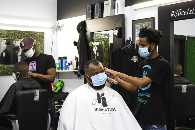 Mohammed Aliyu, left, and Henok Gemeda, right, style customers' hair at K Signature Slice Barber Shop on Lake Street in Minneapolis on Monday, July 13, 2020. Aliyu will open his second Minneapolis shop in Dinkytown.  (Henry Kueppers/The Minnesota Daily via AP)