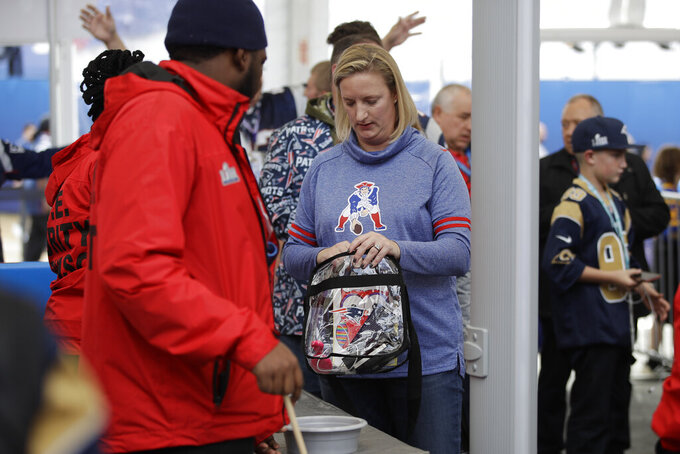 Fans are screened by security as they enter the grounds near the Mercedes-Benz Stadium, Sunday, Feb. 3, 2019, in Atlanta, ahead of the NFL Super Bowl 53 football game between the Los Angeles Rams and New England Patriots. (AP Photo/Matt Rourke)