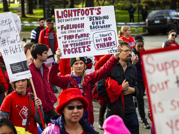 Chicago Teachers Union members and their supporters march through the Near West Side after a rally in Union Park on day five of a Chicago Public Schools district-wide strike, Monday, Oct. 21, 2019. Chicago Public Schools announced Sunday night that classes and after school activities are canceled Monday as the strike enters its first full week. The work stoppage began on Thursday. (Ashlee Rezin Garcia/Chicago Sun-Times via AP)