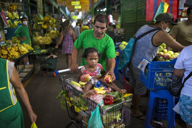 "In this March 18, 2020 photo, Cesar Alegre, accompanied by his 4-year-old daughter Lia, places a damaged apple in his shopping cart filled with discarded produce given to him by vendors at a popular market in Lima, Peru. It is a task that was hard at the best of times, but with a month-long quarantine to curb the spread of the new coronavirus that has forced millions of Peruvians to stay home and closed restaurants and food kitchens, it has become much harder to feed his children. ""The virus has highlighted the selfishness that man carries inside,"" said Alegre.  (AP Photo/Rodrigo Abd)"