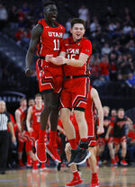 Utah's Both Gach, left, and Rylan Jones celebrate after a play against Kentucky during the second half of an NCAA college basketball game Wednesday, Dec. 18, 2019, in Las Vegas. (AP Photo/John Locher)