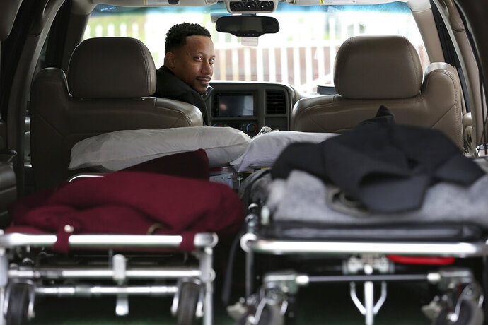 Preston Griffin, who runs First Class Mortuary Transport, poses for a portrait inside his vehicle after delivering a body to the Alfonso Cannon Funeral Chapels in Philadelphia, Pa. on May 6, 2020. (David Maialetti/The Philadelphia Inquirer via AP)