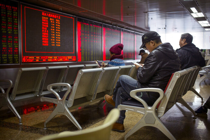 Chinese investors monitor stock prices at a brokerage house in Beijing, Wednesday, Oct. 30, 2019. Shares have declined in Asia after weak earnings for technology and media companies led stocks lower on Wall Street. The modest pullback came a day after the S&P 500 hit an all-time high. (AP Photo/Mark Schiefelbein)