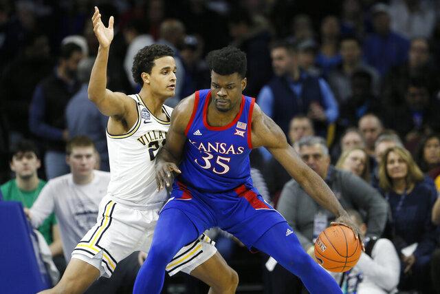 Kansas's Udoka Azubuike (35) tries to dribble past Villanova's Jeremiah Robinson-Earl (24) during the first half of an NCAA college basketball game, Saturday, Dec. 21, 2019, in Philadelphia. (AP Photo/Matt Slocum)