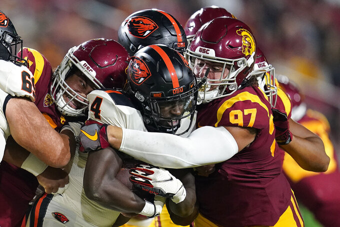 Oregon State running back B.J. Baylor (4) is tackled by a group of Southern California defenders including defensive lineman Jacob Lichtenstein (97) during the first half of an NCAA college football game Saturday, Sept. 25, 2021, in Los Angeles. (AP Photo/Marcio Jose Sanchez)