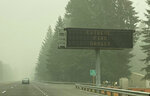 A fire warning sign is seen through the smoke in Sandy, Ore., on Monday, Sept. 14, 2020. Gov. Kate Brown said Monday she has asked President Donald Trump to issue a major disaster declaration for Oregon as it battles deadly wildfires that have wrought destruction across the state. (AP Photo/Rachel La Corte)