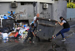 Protesters move a garbage container to block a main road, during a protest against the increase in prices of consumer goods and the crash of the local currency, in Beirut, Lebanon, Thursday, June 17, 2021. Shops, government offices, businesses and banks shut their doors Thursday in response to a call for a general strike by Lebanon's main labor union. (AP Photo/Hussein Malla)