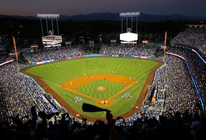 FILE - In this Oct. 25, 2017, file photo, the Houston Astros and the Los Angeles Dodgers play in Game 2 of the baseball World Series at Dodger Stadium in Los Angeles. Dodger Stadium's 40-year wait to host the All-Star Game is going to last even longer. The game scheduled for July 14 was canceled Friday, July 3, 2020, because of the coronavirus pandemic, and Dodger Stadium was awarded the 2022 Midsummer Classic. (AP Photo/Tim Donnelly, File)