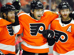 Philadelphia Flyers' James van Riemsdyk, center, is joined by Jakub Voracek, left, and Sean Couturier, right has he celebrates his goal during the second period of an NHL hockey game against the Tampa Bay Lightning, Saturday, Nov. 17, 2018, in Philadelphia. (AP Photo/Tom Mihalek)